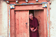 China, Yunnan province, Zhongdian, AKA Shangri-La Songzalin Temple a monk in a door way