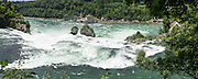 The Rhine Falls (Rheinfall in German) is the largest-volume waterfall in Europe. The falls are on the High Rhine between the municipalities of Neuhausen am Rheinfall and Laufen-Uhwiesen, near the town of Schaffhausen in northern Switzerland, between the cantons of Schaffhausen and Zürich. Rhine Falls are 150 m (450 ft) wide and 23 m (75 ft) high. Winter average water flow is 250 cubic meters per second; while summer averages 700 cubic meters per second. The highest flow ever measured was 1250 cubic meters per second, in 1965; and the lowest, 95 cubic meters per second, in 1921. Rheinfall formed in the last ice age, about 14,000 to 17,000 years ago, by erosion-resistant rocks narrowing the riverbed. This image was stitched from multiple overlapping photos.