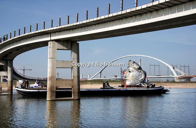 Nederland, Millingen, Nijmegen, 8-4-2030 Vandaag werd een replica van een Romeins masker vervoerd van de scheepswerf in Millingen aan de Rijn naar Het Lentereiland in de nevengeul bij Nijmegen. Het beeld van 6 meter hoog wordt daar geplaatst om als blikvanger en uitkijkpunt te dienen voor de oude stad. Het origineel bevindt zich in museum het Valkhof. De maker en ontwerper is kunstenaar Andreas Hetfeld.Foto: Flip Franssen