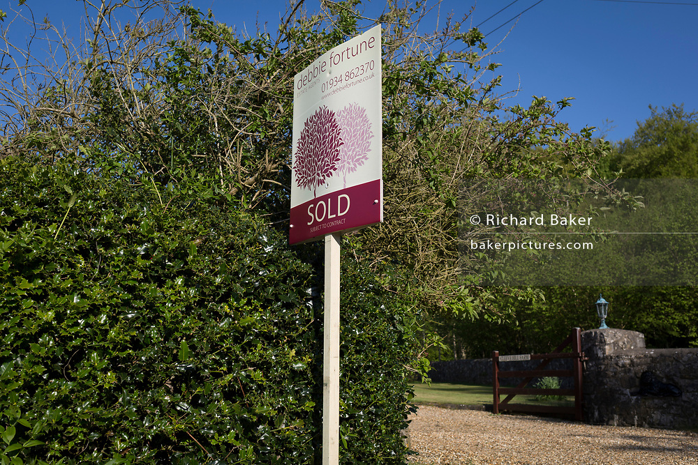 A Sold sign from a local north Somerset estate agency outside a rural property, on 5th May 2018, in Wrington, North Somerset, England.