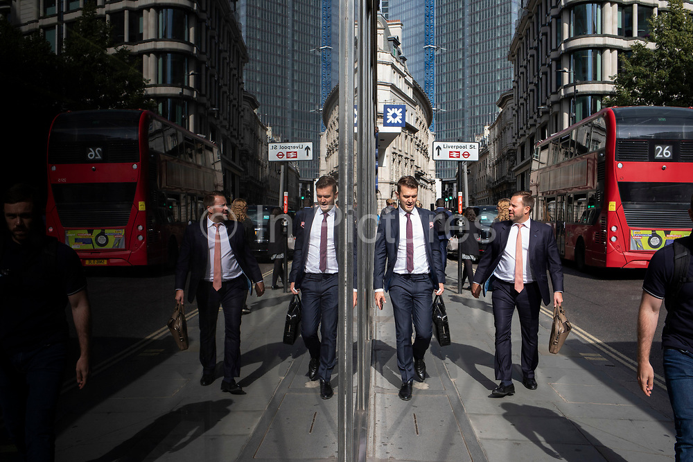 Street scene of city workers and other people reflected in plate glass of modern buidlings in the City of London, England, United Kingdom.