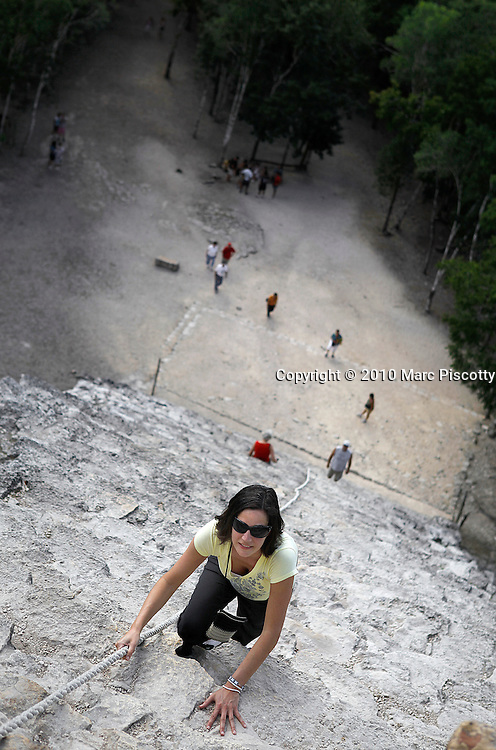 SHOT 12/6/10 12:13:12 PM - Margaret Ebeling of Denver, Co. climbs the steep steps up the side of the Nohoch Mul pyramid at Coba in Mexico. The site contains several large temple pyramids, the tallest, in what is known as the Nohoch Mul group of structures, being some 42 metres (138 ft) in height. Coba is estimated to have had some 50,000 inhabitants (and possibly significantly more) at its peak of civilization, and the built up area extends over some 80 km². The site was occupied by a sizable agricultural population by the 1st century. Coba (Cobá in the Spanish language) is a large ruined city of the Pre-Columbian Maya civilization, located in the state of Quintana Roo, Mexico. (Photo by Marc Piscotty / © 2010)
