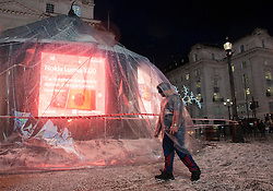 "© Licensed to London News Pictures.23/12/2013. London, UK. Security staff stand in the ""snow"" from the globe whilst protecting the Eros statue snow globe in Piccadilly Circus London today, 23rd December 2013,  after it was damaged by high winds and heavy rain. Photo credit : Peter Kollanyi/LNP"