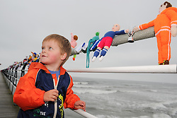 © Licensed to London News Pictures. <br /> 24/05/2014. <br /> <br /> Saltburn, United Kingdom.<br /> <br /> Bradley Smith (L), 3, from Doncaster enjoys the World Cup themed knitted figures that appeared over night on Saltburn pier.<br /> <br /> The Saltburn Yarn Stormers, a secret group of knitters based around the town have struck once again and produced their latest work in the build up to the World Cup by creating knitted figures representing the countries taking part in the World Cup in Brazil later in the year.<br /> <br /> The identities of the group members which remains a secret launched their most recent creation in the early hours to avoid possible detection and secretly gathered to attach the figures to the railings on the Victorian pier in the town before melting away back in to the shadows.<br /> <br /> Photo credit : Ian Forsyth/LNP
