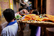 A dead woman carried on a bier through the narrow streets and alleys to Manikarnika Ghat, the main cremation ghat of Varanasi, India. To be cremated in the sacred city of Varanasi means a straight passage to heaven, many Hindus believe.
