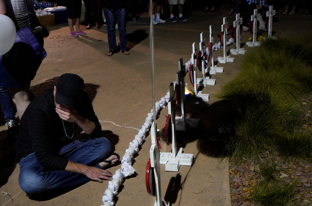 Michael McCabe looks at a photo of Rebecca Wingo, his former girlfriend, at a vigil for the Aurora theater shooting on the 5-year anniversary of the tragedy in Aurora, Colorado United States July 20, 2017.  REUTERS/Rick Wilking