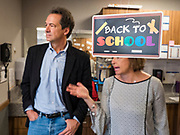 """12 SEPTEMBER 2019 - DES MOINES, IOWA: Governor STEVE BULLOCK (D-MT), left, talks to JEANNINE LAUGHLIN, Area Administrator for New Horizons Academy in front of a """"back to school"""" sign after a Caucus for Kids Facebook Live broadcast sponsored by the Children's Policy Coalition at the school. Gov. Bullock is vying to be the Democratic party's nominee in 2020. He is campaigning in Iowa this week he didn't qualify for the September 12 debate. Iowa traditionally hosts the the first election event of the presidential selection cycle. The Iowa Caucuses will be on Feb. 3, 2020.                  PHOTO BY JACK KURTZ"""