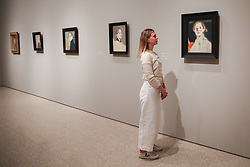 "© Licensed to London News Pictures. 17/07/2019. London, UK. A staff member views Helene Schjerfbeck's painting ""Self-portrait, Black Background 1915"" at Royal Academy of Arts during the preview of her first ever exhibition in the UK. The exhibition features around 65 portraits, landscapes and still life, charting the development of Helene Schjerfbeck's work from a naturalistic style inspired by French Salon painters in the early 1880s, to a radically abstracted and modern approach from the turn of the twentieth century onwards. The exhibition runs  from 20 July to 27 October 2019. Photo credit: Dinendra Haria/LNP"
