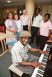 Social worker with multiracial group of older people in Residential home, man playing piano.