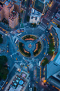 """Columbus Circle, named for Christopher Columbus, is a traffic circle and heavily trafficked intersection in the New York City borough of Manhattan, located at the intersection of Eighth Avenue, Broadway, Central Park South (West 59th Street), and Central Park West, at the southwest corner of Central Park. It is the point from which all official distances from New York City are measured. The name is also used for the neighborhood a few blocks around the circle in each direction. To the south of the circle lies Hell's Kitchen, also known as """"Clinton"""", and the Theater District, and to the north is the Upper West Side. Completed in 1905 and renovated a century later, the circle was designed by William P. Eno – a businessman who pioneered many early innovations in road safety and traffic control – as part of Frederick Law Olmsted's vision for Central Park, which included a """"Grand Circle"""" at the Merchants' Gate, its most important Eighth Avenue entrance.<br /> The monument at the center of Columbus Circle, created by Italian sculptor Gaetano Russo,[1] was erected as part of New York's 1892 commemoration of the 400th anniversary of Columbus' landing in the Americas. Constructed with funds raised by Il Progresso, a New York City-based Italian-language newspaper, the monument consists of a marble statue of Columbus atop a 70-foot (21 m) granite rostral column decorated with bronze reliefs representing Columbus' ships: the Niña, the Pinta, and the Santa María, although actually they are Roman galleys instead of caravels. Its pedestal features an angel holding a globe."""