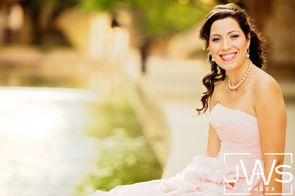 Bride sitting along the Las Colinas Canals in her wedding dress