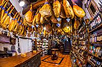 Dry cured ham legs hanging above the shop at Bodega La Moralea, in the mountain village of  Pampaneira, Las Alpujarras, Sierra Nevada National Park, Granada Province, Andalusia, Spain.