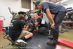 Ziggy and Dave Johnson help Pat Simmons out with his rear wheel at Harley-Davidson of Bloomington where they opened the shop to work on all of the old bikes during the Motorcycle Cannonball Race of the Century. Stage-4 from Chillicothe, OH to Bloomington, IN. USA. Tuesday September 13, 2016. Photography ©2016 Michael Lichter.