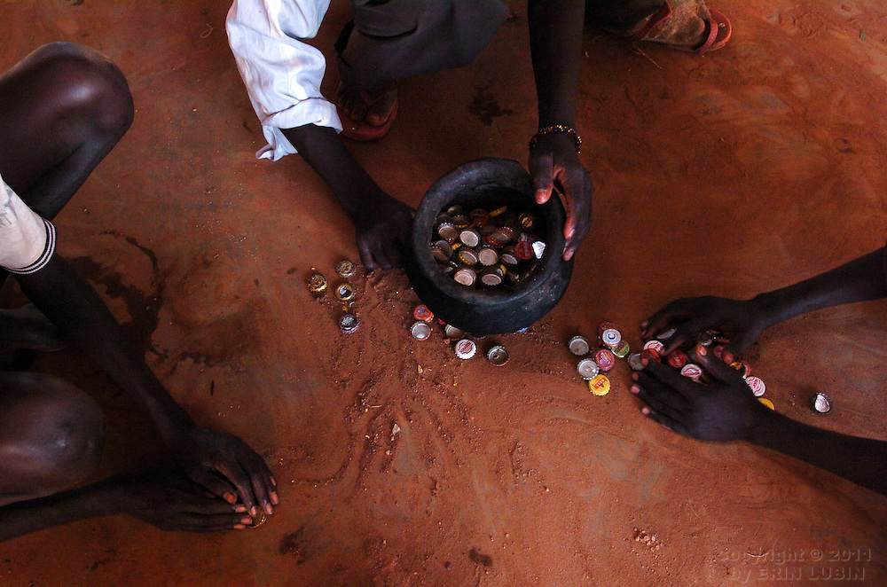 Boys organize bottle caps to clean and use in art projects at The Charity for Peace center in Gulu, north Uganda on October 7, 2006. Charity for Peace, a locally run NGO, was set up in response to the large numbers of children who leave their village homes at night to sleep in the city where they may be protected from the LRA, the Lord's Resistance Army. Gulu is the main base for the UPDF, Uganda Peoples Defense Force, to fight the LRA, Lord's Resistance Army. Since the war began in 1987 over 2 million people have moved from their village homes to camps close to the town of Gulu where they can be protected from the LRA by the UPDF. Over the years the LRA are said to have abducted more than 30,000 children for use as soldiers in their army. The children were often tortured and girls were frequently used as sex slaves. Current peace talks between the Ugandan government and the LRA taking place in Juba, southern Sudan, have the north Ugandan community hoping for an end to the 20 year long war..Photo by Erin Lubin