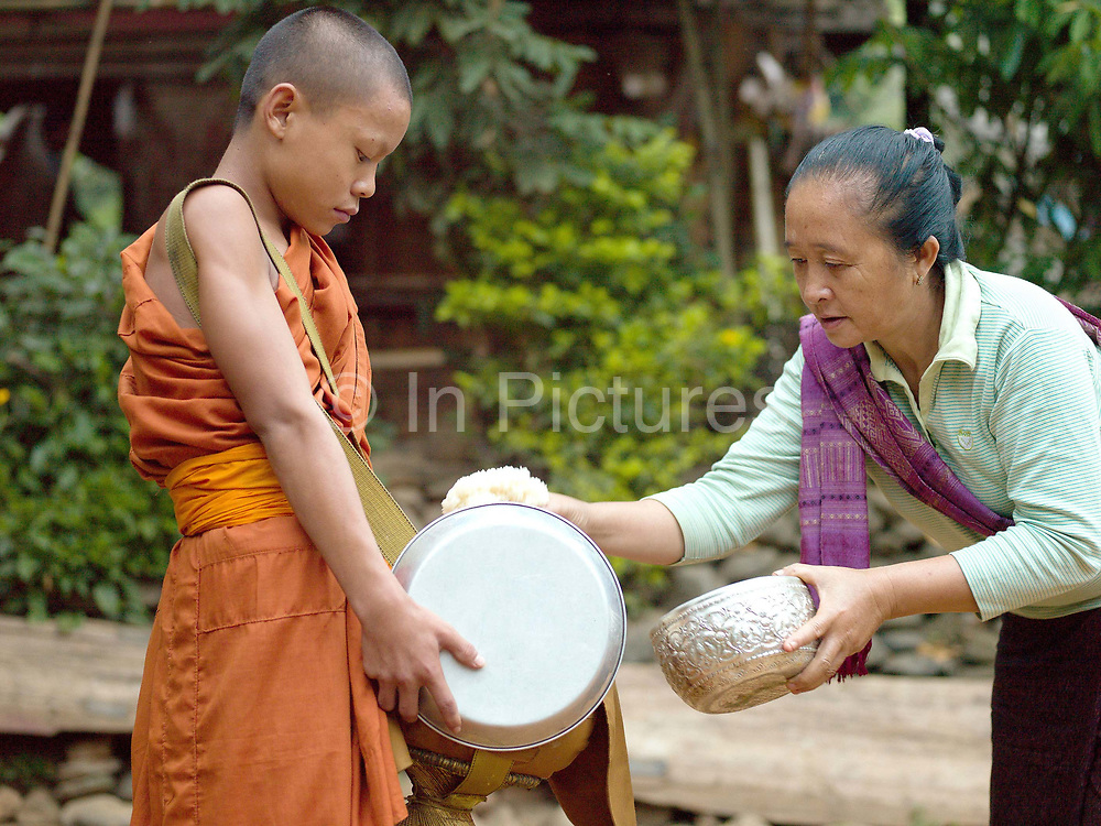 The villagers of Ban Mouanghoun rise early for the daily Buddhist alms giving ceremony (tak bat) donating sticky rice to the monks for their one meal of the day, Phongsaly province, Lao PDR This is an ancient, religious tradition and those who give alms earn merit for their next life. Lao Buddhists are very devout and almost every Lao man joins a monastery, or temple, for at least a short period of time. Many men also become monks for the rest of their lives. The village will be relocated due to the construction of the Nam Ou Cascade Hydropower project Dam 5.