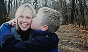 Young son kisses his mother on the cheek while strolling through High Park.