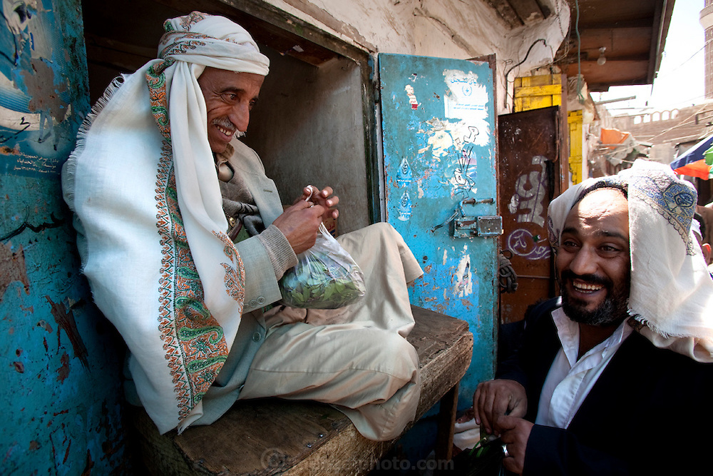 Ahmed Ahmed Swaid, a qat merchant, sits at a market in the old city of Sanaa, Yemen, and sells qat leaves in plastic bags.  (From the book What I Eat: Around the World in 80 Diets.) Ahmed, who wears a jambiya dagger as many Yemeni men do, has been a qat dealer in the old city souk for eight years. Although qat chewing isn't as severe a health hazard as smoking tobacco, it has drastic social, economic, and environmental consequences. When chewed, the leaves release a mild stimulant related to amphetamines. Qat is chewed several times a week by a large percentage of the population: 90 percent of Yemen's men and 25 percent of its women. Because growing qat is 10 to 20 times more profitable than other crops, scarce groundwater is being depleted to irrigate it, to the detriment of food crops and agricultural exports.  MODEL RELEASED.