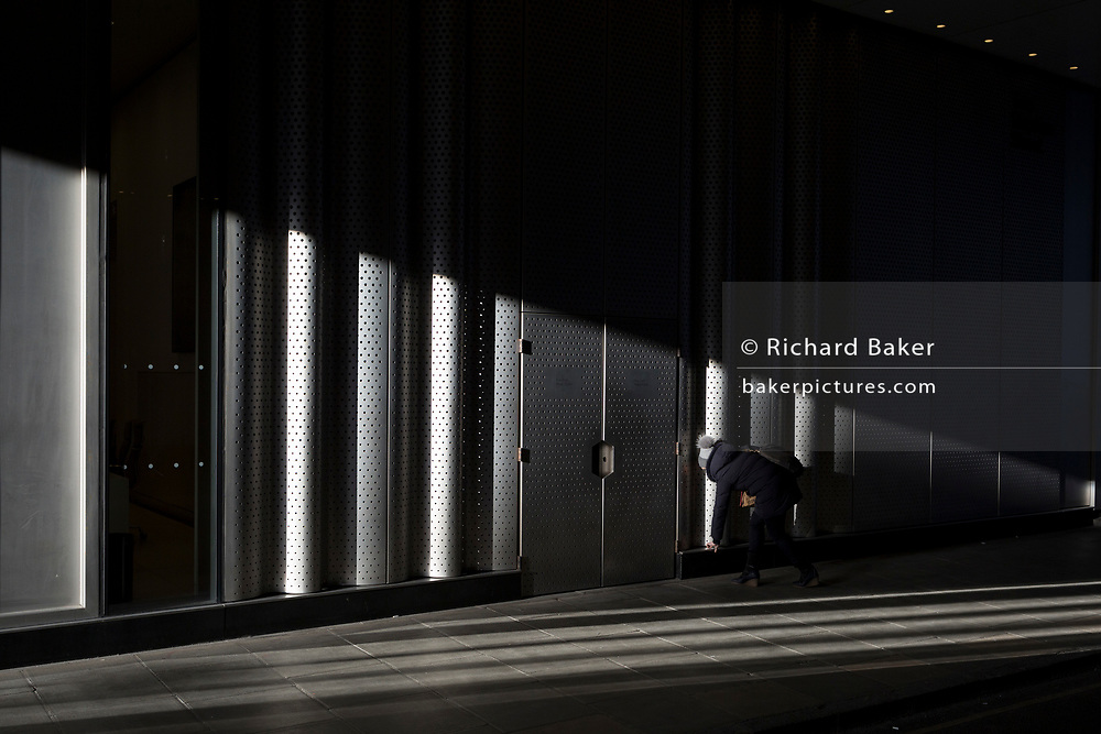 A person stops to pick up an object in a shaft of sunlight, on 7th February 2018, in London, England.