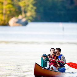 A family canoeing on Pawtuckaway Lake in New Hampshire's Pawtuckaway State Park.