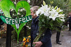 London, UK. 14 June, 2019. Flowers are brought into the memorial service at St Helen's Church to mark the second anniversary of the Grenfell Tower fire on 14th June 2017 in which 72 people died and over 70 were injured.