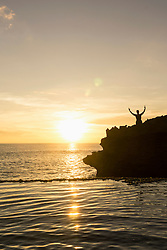 Silhouette of a man standing with arms outstretched on cliff during sunset, Nusa Lembongan, Bali, Indonesia