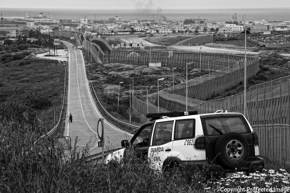 MELILLA, SPAIN - APRIL 21, 2010 : The Guardia Civil  controls  the  road between  the borders of Beni Enzar and the  El Barrio Chino on April 21 , 2010 in Melilla. Spain. Every day at the pedestrian border of El Barrio Chino hundreds of people are involved in transporting smuggled goods from Melilla a Spanish enclave on the North African coast to Morocco.For each package introduced in morocco receive between 3 an 5 euros depending on size,with a little luck achieved make three trips a day.It is estimated that from Monday to Thursday on foot enter Melilla 8.000 porters, mostly women, to return to Morocco with huge sacks of goods from the warehouse border area of Beni Enzar in Melilla .( Photo by Jordi Cami )