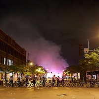 Protesters loot and burn businesses while the Minneapolis Police bike officers cordon off the area near the Minneapolis Police third precinct after a white police officer was caught on a bystander's video pressing his knee into the neck of African-American man George Floyd, who later died at a hospital, in Minneapolis, Minnesota, U.S. May 28, 2020. REUTERS/Adam Bettcher
