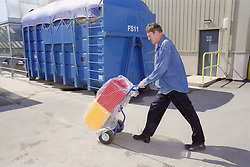 Man with disability pushing materials on trolley,