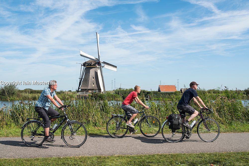 Cyclists on path and windmill at Kinderdijk UNESCO World Heritage Site in The Netherlands