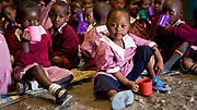School children eat their morning porridge before lessons commence.<br /> It is school policy that all the children wear their uniform; not only does it make the children immediately identifiable, and everyone in community knows where a child comes from and belongs, but it also safeguards against child trafficking. The Uniforms are made affordable, as they are sourced locally.  They can also be subsidised, in exchange for parental involvement, for children from poorer homes. It is a good a way of getting the support of the community and for all children to be equal at school.