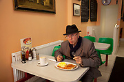 "Dave, a local Elvis impersonator, having his lunch of baked beans on toast and eggs in a greasy spoon cafe in North London. The greasy spoon caf is a British institution where people can buy cheap food in simple surroundings. They are visited by poor and affluent alike. Greasy spoon is a colloquial or slang term originating in the United States of America to mean a small, especially cheap, archetypal working class restaurant or diner. The term is now used in many English speaking countries to mean the same thing. The name ""greasy spoon"" is used to imply a less-than-rigorous approach to hygiene and appears in use in the early 20th century."