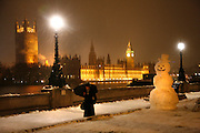 Weather, climate change. London, Britain and Europe, is gripped by a big freeze. Winter conditions which are likened to Siberia swept across Europe, bringing traffic and transport to a halt, closing schools and stopping millions of people going to work. Whilst most buses and tubes were not working, some commuters and tourists got to central London to enjoy the freak snow.///At night, commuters and tourists walk past a huge snowman wearing a hat stands on the opposite bank of the Thames river to the Westminster and the Houses of Parliament
