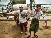03 NOVEMBER 2015 - YANGON, MYANMAR: Men move empty oil barrels on the Yangon docks.    PHOTO BY JACK KURTZ