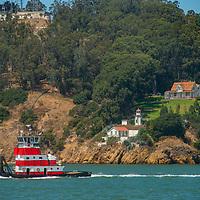 A tug boat motors past an old lighthouse on Yerba Buena Island in San Francisco Bay, California.