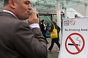 A man stands smoking in front of a no smoking sign outside the  2010 World Travel Market, Excel Centre, London. UK