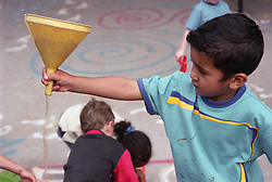Nursery school boy playing with sand in playground,