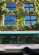 A bus passes the Musee du Quai Branly, where plants grow up the exterior walls, in Paris, France