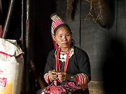 A Ko Loma ethnic minority woman sews traditional clothing in her home, Ban Lao Leo, Phongsaly province, Lao PDR. One of the most ethnically diverse countries in Southeast Asia, Laos has 49 officially recognised ethnic groups although there are many more self-identified and sub groups. These groups are distinguished by their own customs, beliefs and rituals. Details down to the embroidery on a shirt, the colour of the trim and the type of skirt all help signify the wearer's ethnic and clan affiliations.