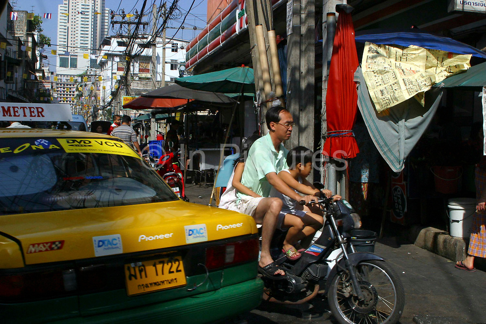 A Thai family of 3 travel on a scooter pass a taxi on the streets of Bangkok, Thailand