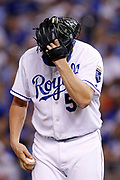 Kansas City Royals relief pitcher Greg Holland covers his head between pitches against the Miami Marlins during a baseball game at Kauffman Stadium in Kansas City, Mo., Tuesday, Aug. 13, 2013. (AP Photo/Colin E. Braley)