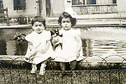 vintage portrait of two little girls sitting by a courtyard water fountain France