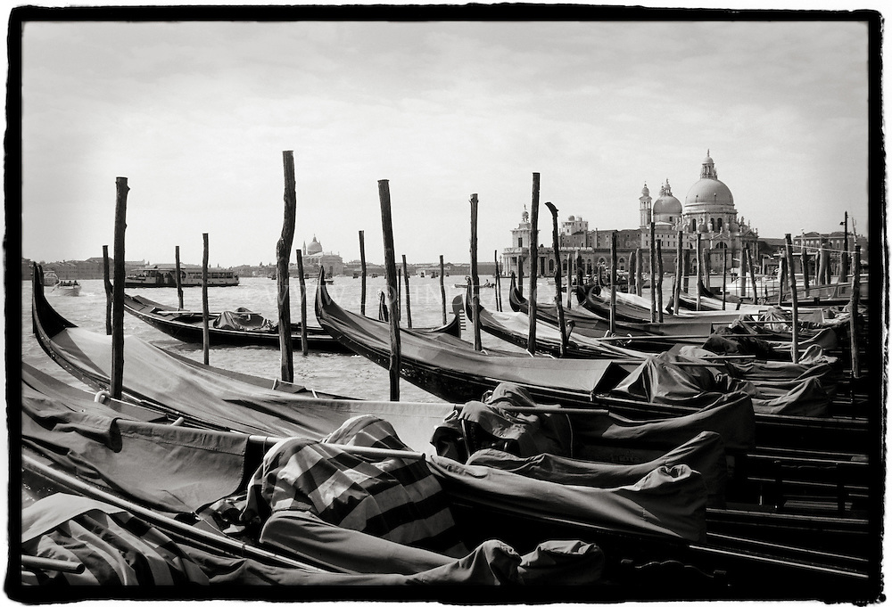 Black and white photo of Gondolas lined up on the water in Venice, Italy.