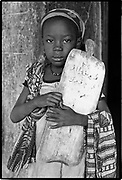 A child is a store; what you tell her, she keeps.  Ugandan proverb<br /> <br /> This Muslim girl attends a Koranic (religious) school where lessons are in Arabic. The board she carries serves as her writing pad. Sokoto, Nigeria  1989