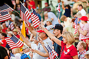 """May 29 - TEMPE, AZ: People wave American flags during a rally against illegal immigration in Tempe, AZ, Saturday. About 3,000 people attended a """"Buy Cott Arizona"""" rally at Tempe Diablo Stadium in Tempe, AZ Saturday night. The rally was organized by members of the Arizona Tea Party movement to show support for Arizona law SB1070. The """"Buy Cott"""" is a reaction to the economic boycott planned by opponents of SB1070. SB1070 makes it an Arizona state crime to be in the US illegally and requires that immigrants carry papers with them at all times and present to law enforcement when asked to. Critics of the law say it will lead to racial profiling, harassment of Hispanics and usurps the federal role in immigration enforcement. Supporters of the law say it merely brings Arizona law into line with existing federal laws.  Photo by Jack Kurtz"""