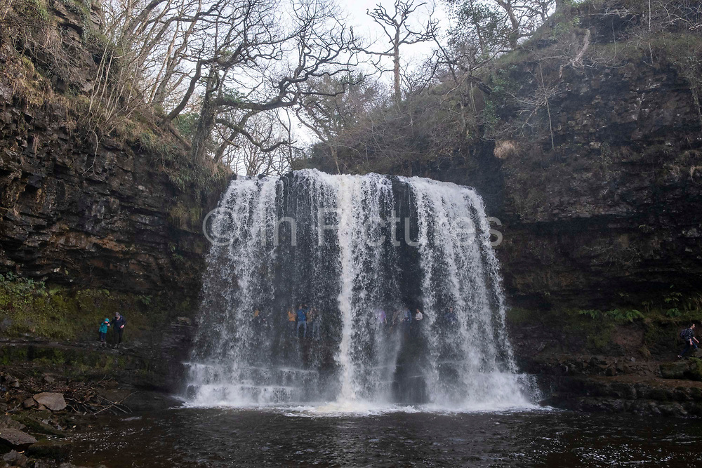 People explore and go behind the Sgwd Yr Eira Waterfall in the Afon Hepste River in Brecon Beacons Waterfall Country National Park, Wales, Powys, United Kingdom. This waterfall is famous as one of the only waterfalls in Wales that you can walk behind.