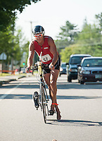 Bruce Butterworth dismounts his bike as he enters the transition area at Opechee Park during GLCAC's Marshmallow Man Sprint Triathlon on Sunday morning.  (Karen Bobotas/for the Laconia Daily Sun)