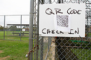 A sign with a QR code that must be scanned by each member of the North Dallas Bulldog football team before entering the field is a clear reminder of the dangers of the current Covid-19 pandemic on the first day of practice.  (Photo by Jaime R. Carrero)
