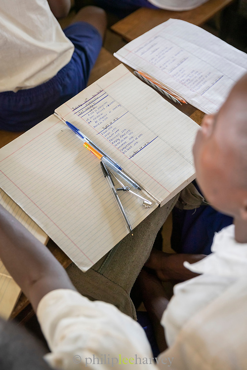High angle view of schoolboy at desk with textbook and pencils, The Musoto Christian School, Uganda