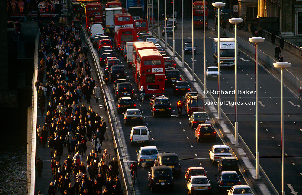 Seen from an office block high vantage point, thousands of commuters pour northwards over London Bridge against the direction of queueing buses and cars. It is a scene about the transient business community and mass transport. The working population arrives early for work over the bridge in the City of London's historic financial district. We see the sunlit faces of those walking towards the viewer which echo the red tail lights of the stationary vehicles. So gridlocked is the traffic on the southbound carriageway, there is a lone cyclist stuck and squeezed between the curb and a double-decker bus. The City of London has a resident population of under 10,000 but a daily working population of 311,000. The City of London is a geographically-small City within Greater London, England. ...