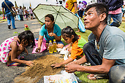 13 MAY 2013 - BANGKOK, THAILAND: A man sells blessed rice seeds his family (background) collected at the Royal Ploughing Ceremony. After the ceremony, thousands of Thais, mostly family formers, rush onto the ploughed ground to gather up the blessed rice seeds sown by the Brahmin priests. The Royal Plowing Ceremony is held Thailand to mark the traditional beginning of the rice-growing season. The date is usually in May, but is determined by court astrologers and varies year to year. During the ceremony, two sacred oxen are hitched to a wooden plough and plough a small field on Sanam Luang (across from the Grand Palace), while rice seed is sown by court Brahmins. After the ploughing, the oxen are offered plates of food, including rice, corn, green beans, sesame, fresh-cut grass, water and rice whisky. Depending on what the oxen eat, court astrologers and Brahmins make a prediction on whether the coming growing season will be bountiful or not. The ceremony is rooted in Brahman belief, and is held to ensure a good harvest. A similar ceremony is held in Cambodia.    PHOTO BY JACK KURTZ